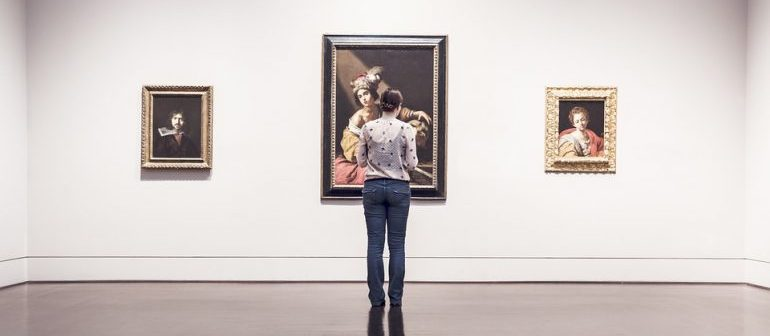 Woman watching paintings on the wall