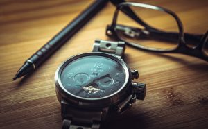 Watch, glasses and a pen on a table