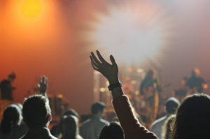 People waving hands at a concert