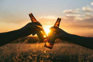 Close up of two hands holding beer bottles.