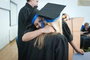 Two graduates hugging