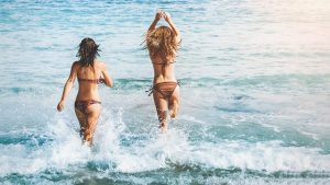 Two girlfriends going for a swim.