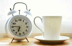 White clock next to a white mug.