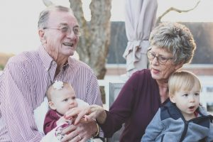 Ways to spend your retirement - old couple holding their grandchildren.