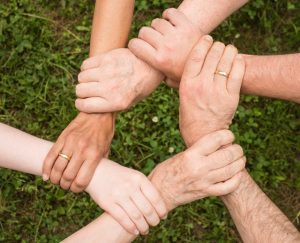 Close up of people holding hands.