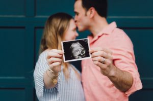 Man and woman in front of a house door holding an ultrasound photo.