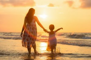 Mother and daughter enjoying sunset on the beach.