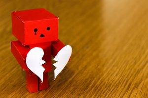 A paper figure holding a broken heart