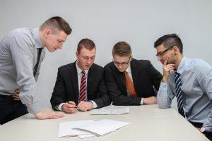Four men sitting at a desk.