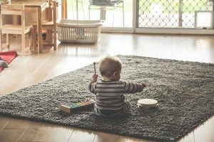 A toddler playing on the floor.