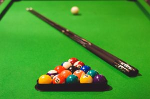 Pool table with balls and cues.