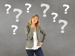 A woman wondering under question marks