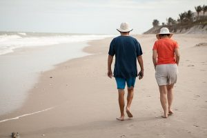 Elderly couple walking on the beach in Florida.