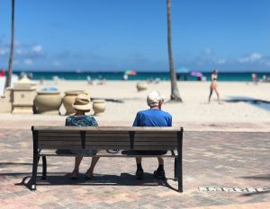 Senior couple on a beach bench.