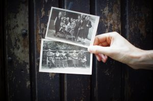 Person holding old photographs.