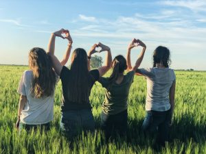 Find a roommate in Deerfield Beach FL- Four girls sitting on the grass making a hart shape with their hands