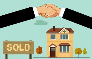An image of a house being sold and two people shaking hands.