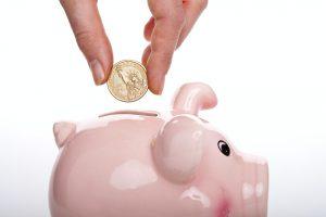 A woman putting a coin into a piggy bank