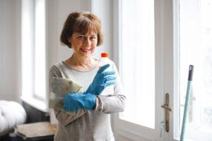 A woman with cleaning supplies for sanitizing the home before moving in