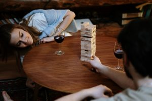 A couple enjoying a glass of wine and playing Jenga together