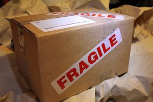 "A sealed moving box with a ""fragile"" mark in red letters; packing fragile items neatly actually helps make your move to Daytona Beach easier"