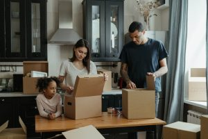 A family of three, mother, father and daughter unpacking their moving boxes in the kitchen