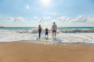 A mother, father and their daughter holding hands on the coast; this family bliss is among the biggest reasons to move to Daytona Beach.