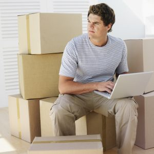 A man sitting on a pile of boxes with his laptop, looking away from it, trying to figure out when's the cheapest time to relocate