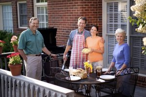Two happy, neighborhood couples enjoying each other's company and a bit of barbecue.