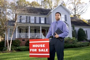 "A man in a blue shirt standing in front of a two-story house next to a red ""For Sale"" sign"