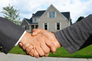 Handshake in front of house