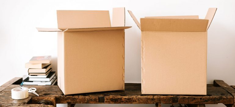 Carton boxes and stacked books on table that best local movers in Crestview can provide you with