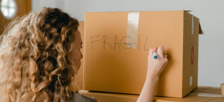 Woman writing note on carton box with marker