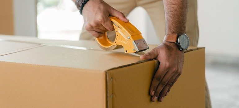 Man taping carrying box with scotch
