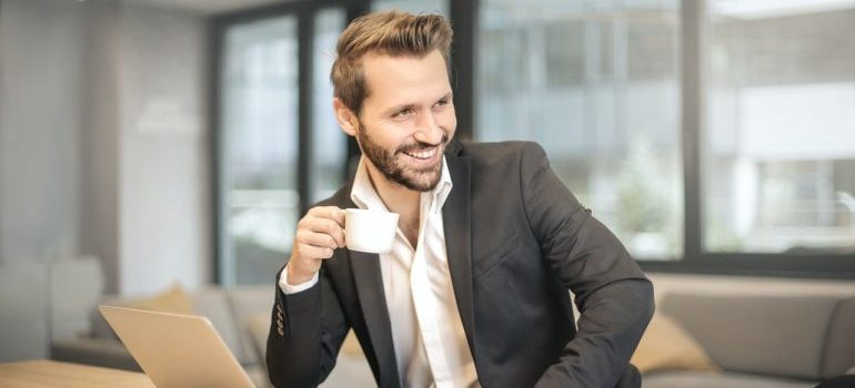 A man drinking a cup of coffee at his desk and smiling.