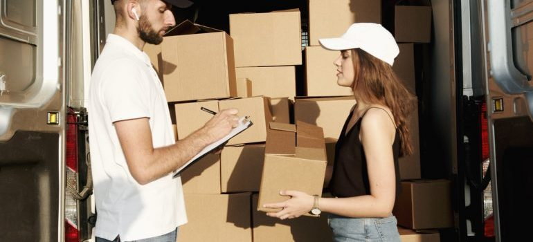 A woman talking to a mover near a van with boxes.