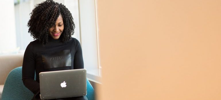 A woman smiling while using her laptop