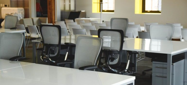 An empty office with white desks and chairs.
