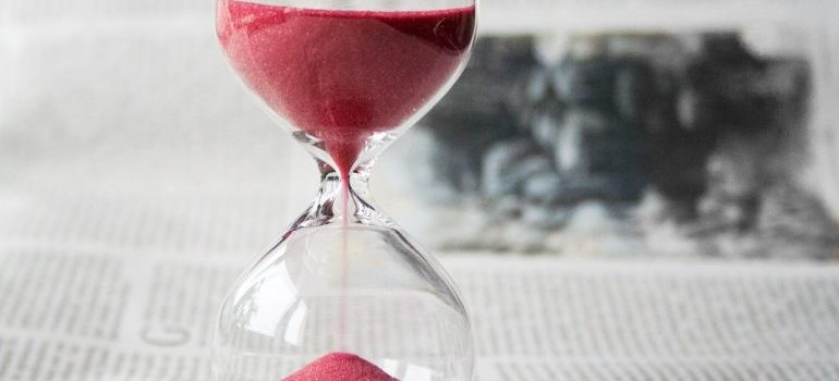 an hourglass with pink sand and the newspaper background