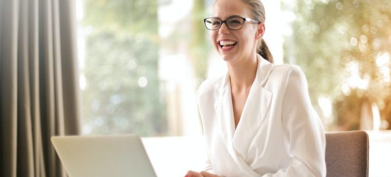 woman siting by a lap top and laughing