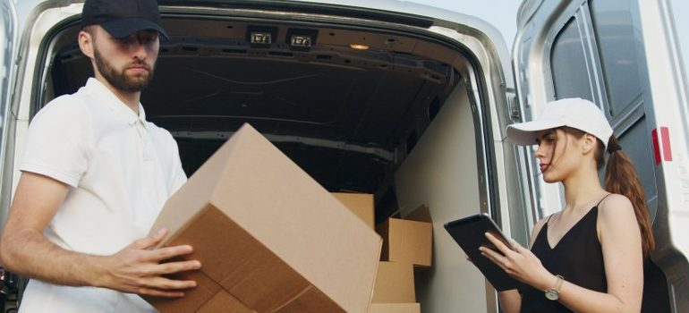 male and female loading a van with cardboard boxes