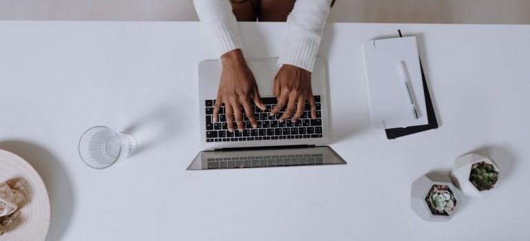 A person typing on a laptop on a white table.