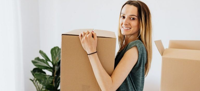 girl carrying a box to long distance movers Port St Lucie