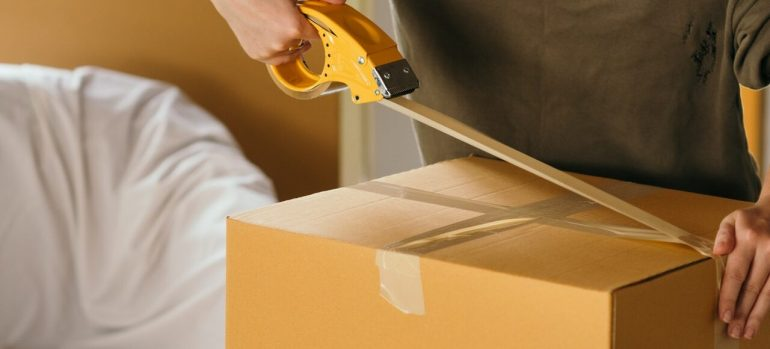 A man applying tape to a cardboard box, before hiring the best long distance movers in Miami Beach.