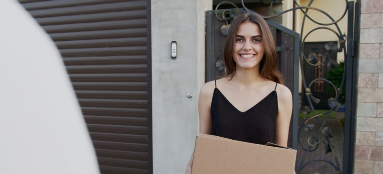 A woman holding a cardboard box in front of a house, before hiring the best long distance movers Miami Beach FL offers.