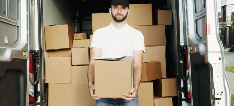 A man in a white shirt carrying a cardboard box in front of other boxes.