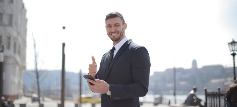A smiling businessman holding a phone and giving thumbs up.