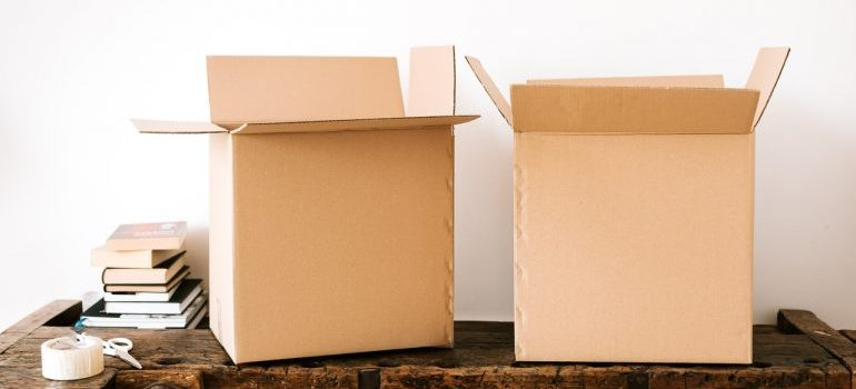 A couple of cardboard boxes on a wooden surface.