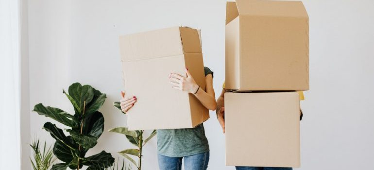 A couple holding large moving boxes.