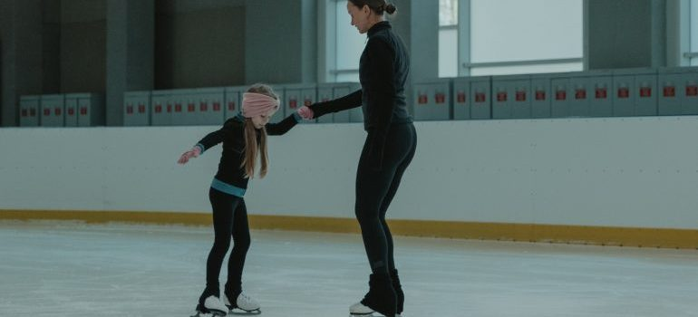 A woman teaches a young girl to skate in an ice arena